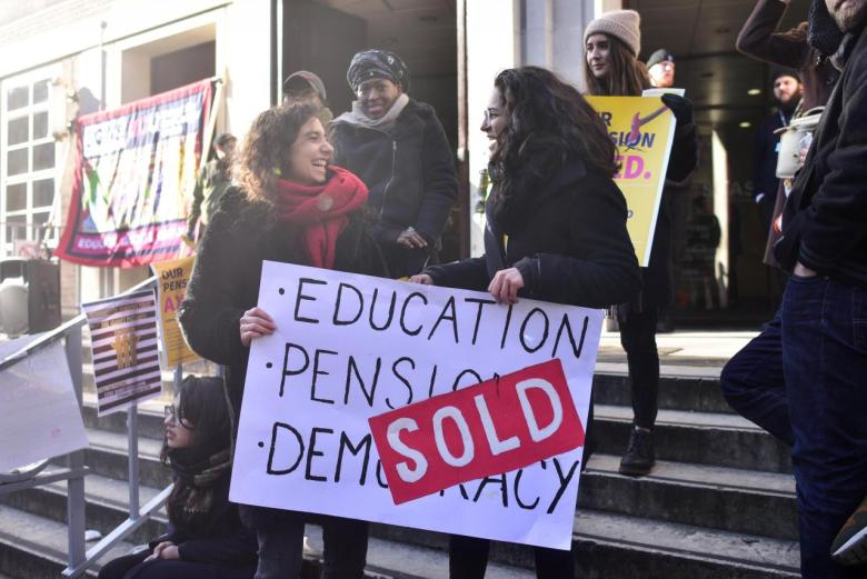 Protesters hold banners outside the University of London